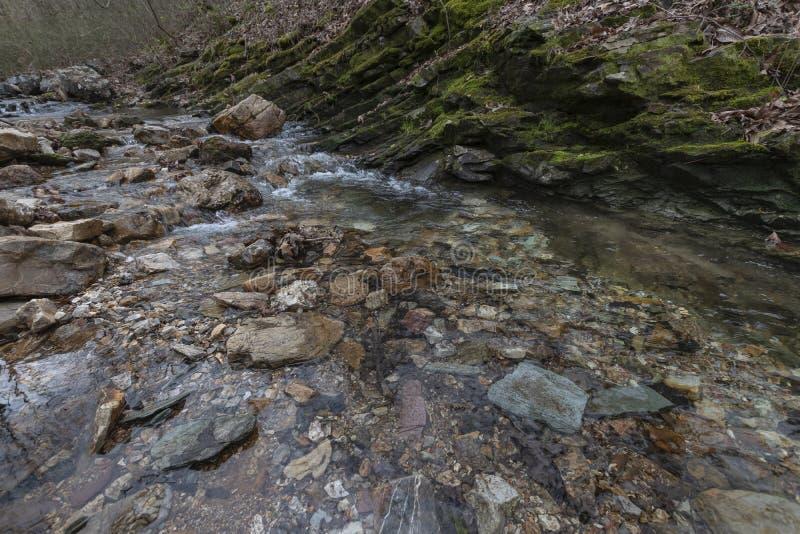 Una piccola cascata del fianco di una montagna nell'estate immagini stock