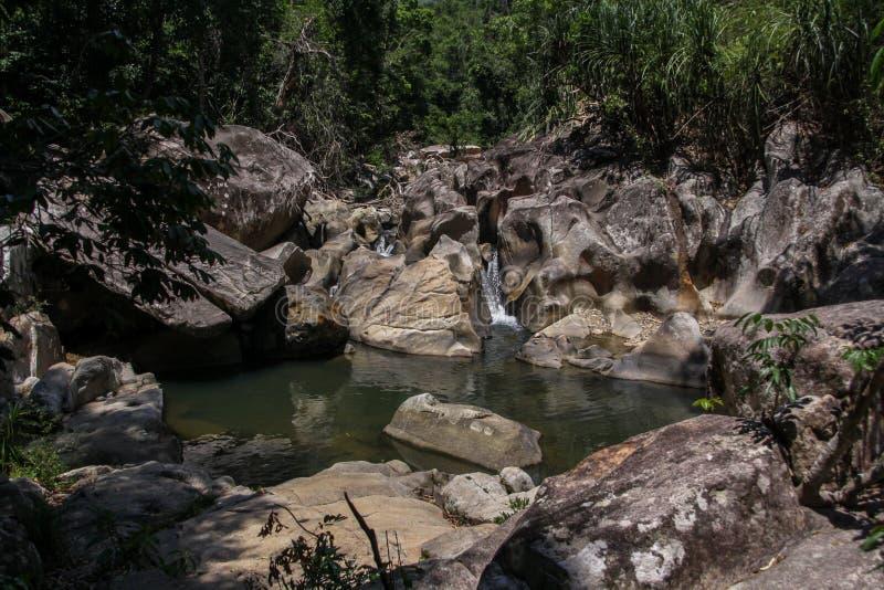 Una piccola cascata e uno stagno selvaggio nelle montagne del Vietnam Rocce ed acqua fotografie stock libere da diritti