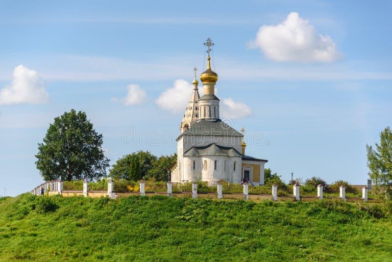 Una piccola chiesa del villaggio su un'alta collina chiesa sulle banche del fiume immagini stock
