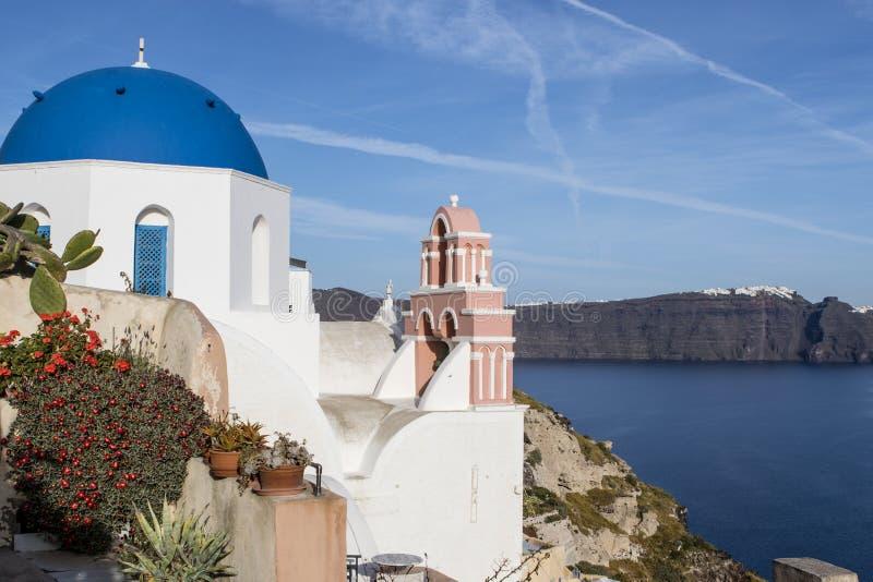 Una piccola chiesa greco ortodossa bianca con un tetto blu tipico sulla scogliera a OIA, Santorini, Cicladi Grecia immagini stock