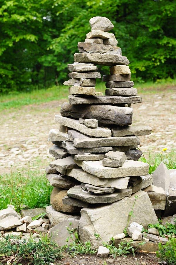 Una piccola costruzione fatta delle pietre che somigliano ad una piramide, pagoda Pietre grige impilate sopra a vicenda nella for immagine stock