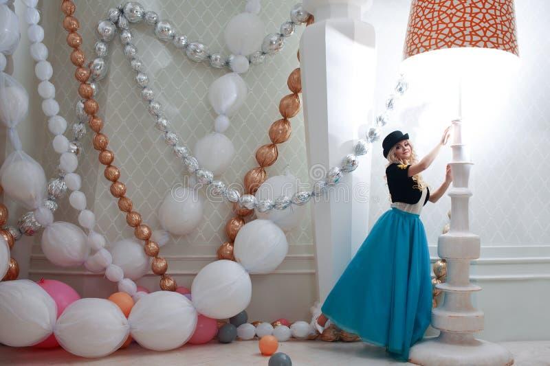 Una piccola donna sotto la grande lampada da tavolo Bella giovane bionda in gonna e cappello blu Regolazione favolosa, dimensione fotografie stock