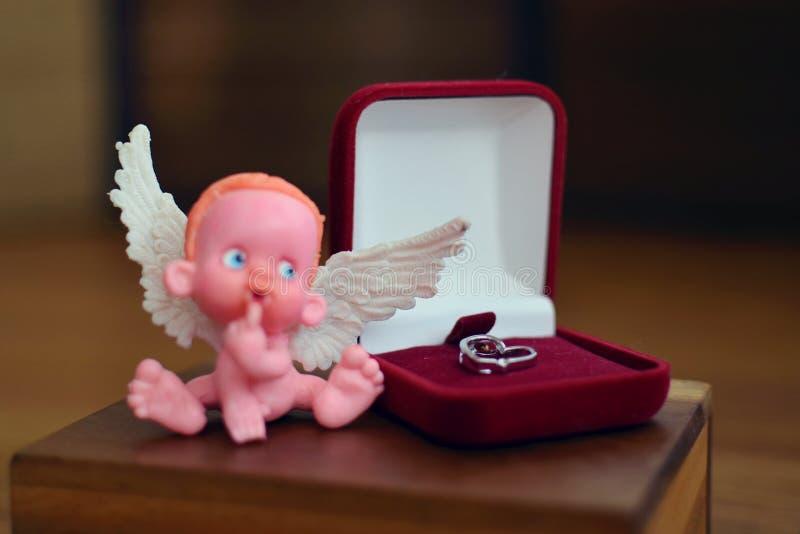 Una piccola figura di un angelo sfuocato che si siede su o vicino ad una fine del contenitore di gioielli su fotografie stock libere da diritti