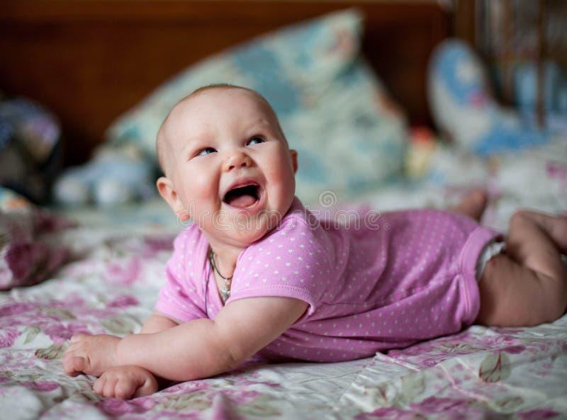 Una piccola neonata nei clithes rosa che si trovano a casa sul letto immagine stock