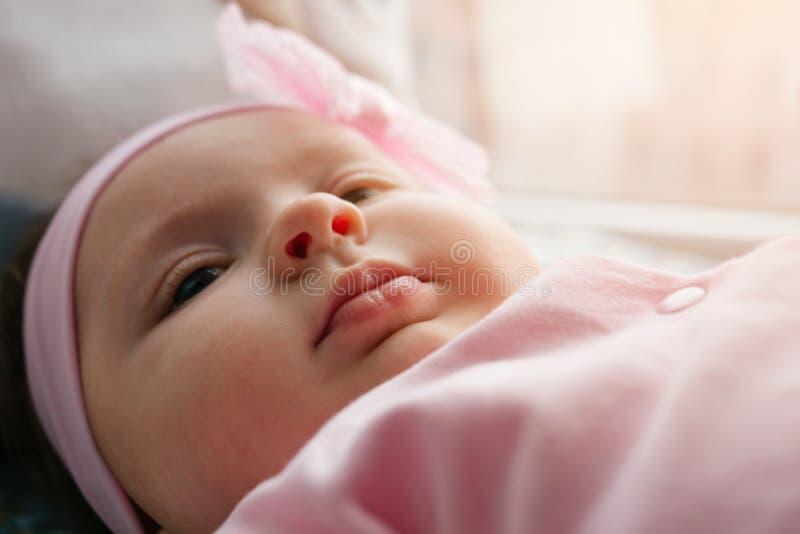 Una piccola neonata si trova su un letto fotografie stock