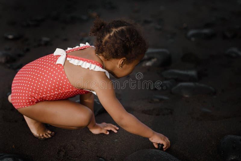 Una piccola neonata sveglia sta giocando su una spiaggia vicino ad un mare fotografie stock libere da diritti