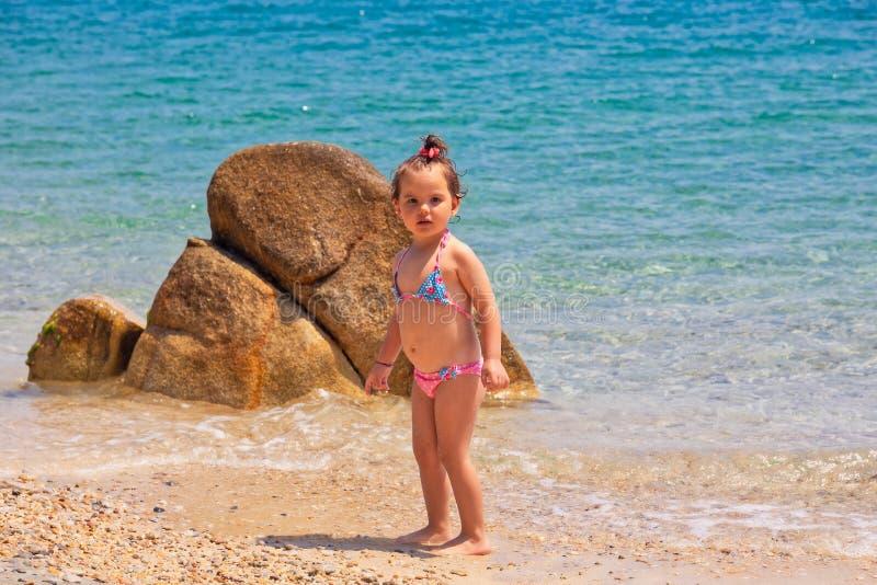 Una piccola neonata sveglia sta giocando su una spiaggia vicino al mare fotografie stock libere da diritti