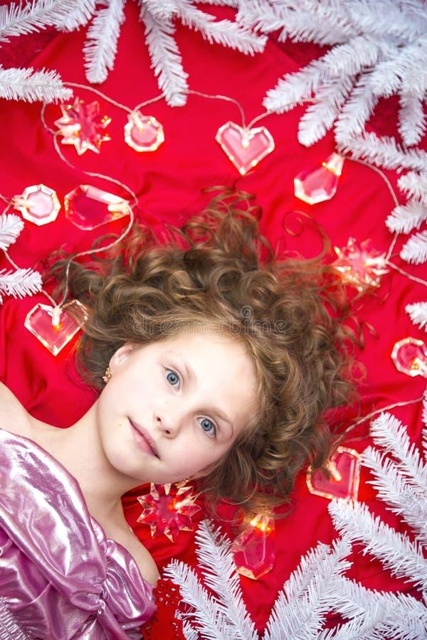 Una piccola ragazza bionda che si trova su un pavimento rosso con una ghirlanda di Natale e sui rami dell'abete intorno lei capa fotografie stock libere da diritti