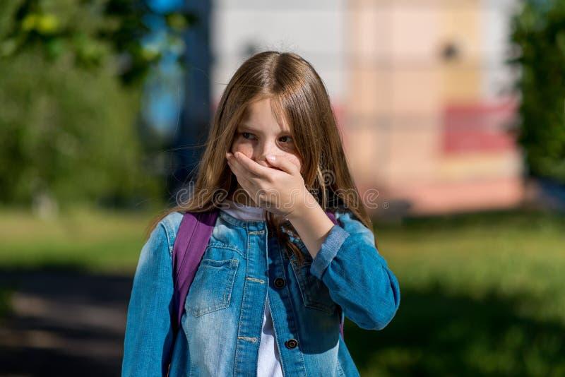 Una piccola ragazza bionda ha coperto la sua bocca di sua mano Emozioni di timore di timore Estate all'aperto in aria fresca E fotografie stock libere da diritti