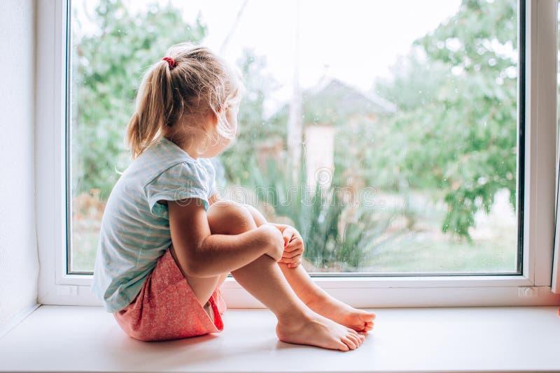 Una piccola ragazza bionda splendida che fissa dalla finestra un giorno piovoso bagnato e freddo immagini stock libere da diritti