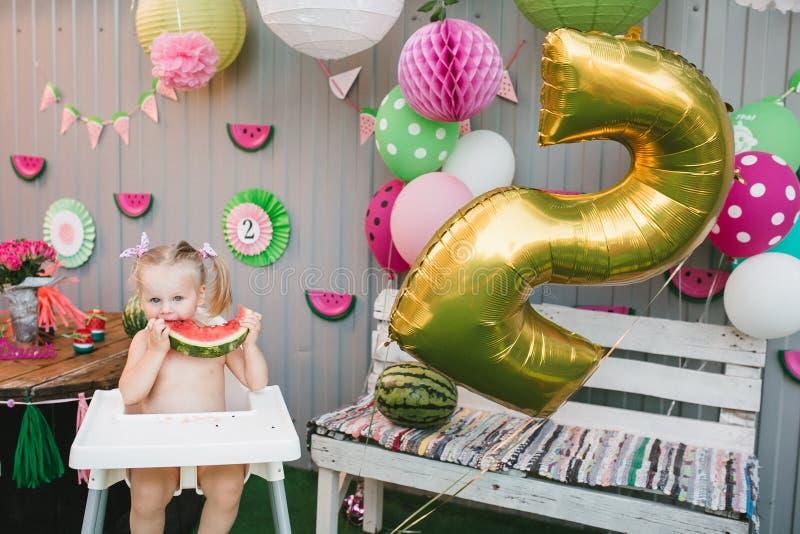 Una piccola ragazza bionda sveglia sta sedendosi in un seggiolone bianco del ` s del bambino e ridendo sta mangiando una fetta di immagini stock libere da diritti