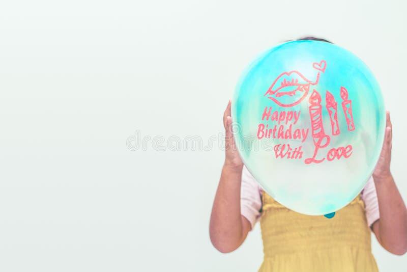Una piccola ragazza che tiene un pallone blu con il messaggio di compleanno fotografia stock