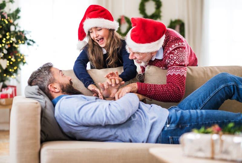 Una piccola ragazza con il nonno che sveglia suo padre addormentato al tempo di Natale fotografie stock