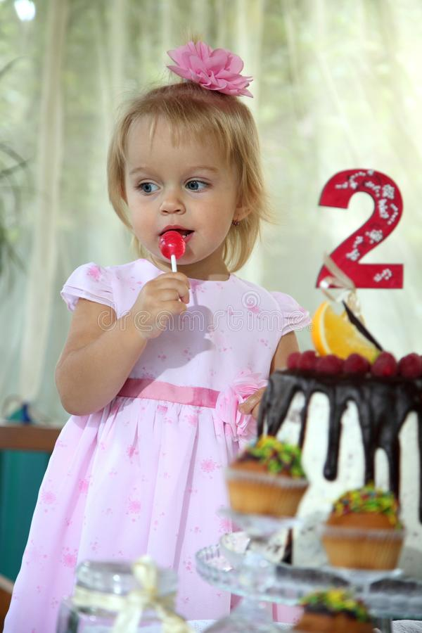 Una piccola ragazza dai capelli bianchi di due anni sta provando una torta di compleanno Bambina che celebra secondo compleanno fotografie stock