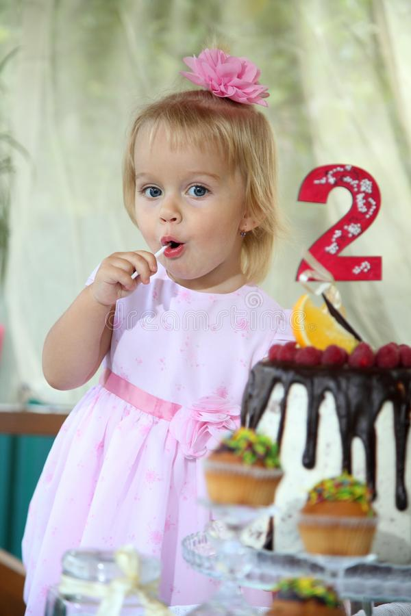 Una piccola ragazza dai capelli bianchi di due anni sta provando una torta di compleanno Bambina che celebra secondo compleanno fotografie stock libere da diritti