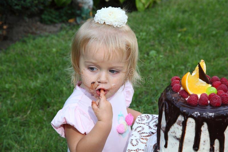 Una piccola ragazza dai capelli bianchi di due anni sta provando una torta di compleanno Bambina che celebra secondo compleanno fotografia stock libera da diritti
