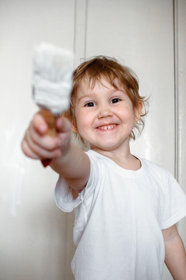 Una piccola ragazza impertinente in una maglietta bianca dipinge la parete con pittura bianca raggiungendo nella macchina fotogra fotografia stock