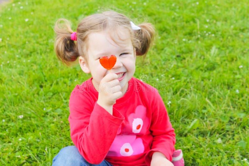 Una piccola, ragazza maligna che tiene una caramella su un bastone Gi grazioso immagine stock libera da diritti