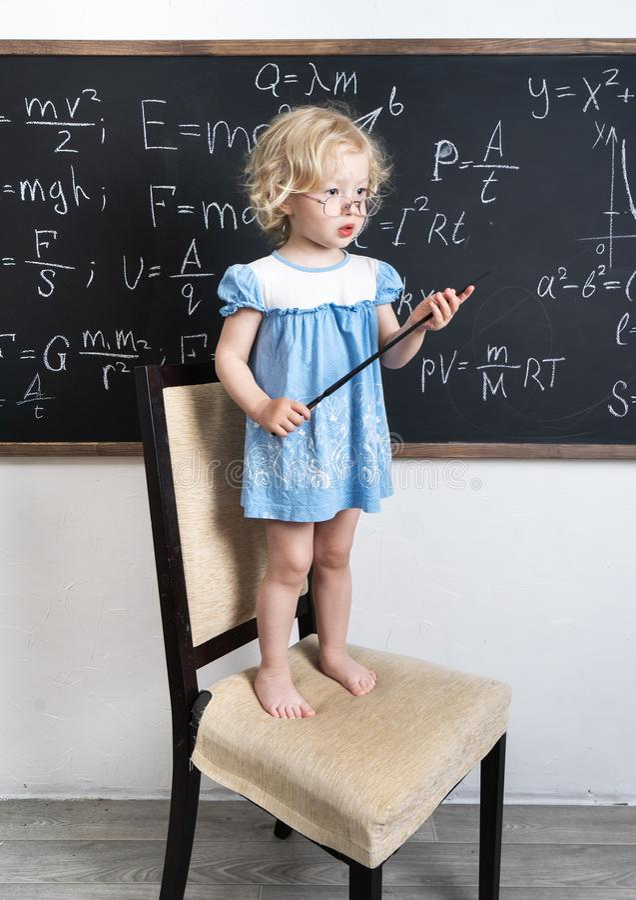 Una piccola ragazza prescolare in vetri sta su un seggiolone alla lavagna e tiene un puntatore in sue mani fotografia stock