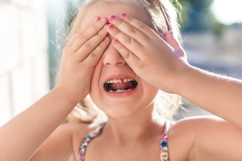 Una piccola ragazza sveglia chiude le mani dei suoi occhi e mostra un dente da latte annaspante fotografia stock libera da diritti