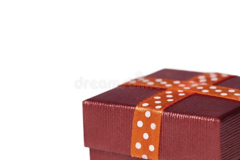 Una piccola scatola attuale arancio classica chiusa con un nastro, frammento isolato su fondo bianco immagini stock