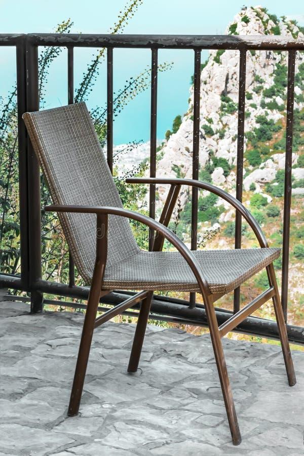 Una piccola sedia di vimini o canna-sedia sul terrazzo o balcone con una bella vista della cima della roccia, del mare blu e del  fotografia stock libera da diritti