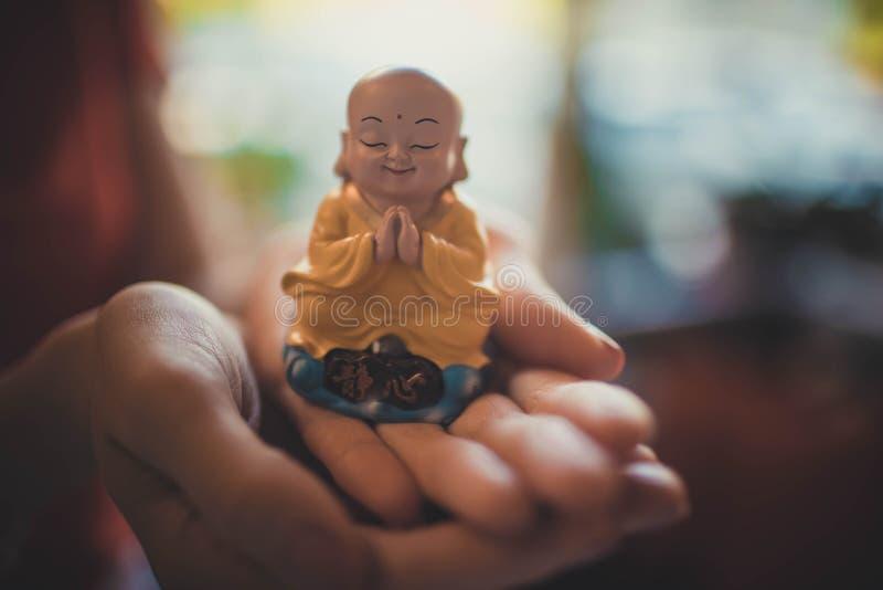 Una piccola statua di Buddha nelle mani di una donna fotografia stock