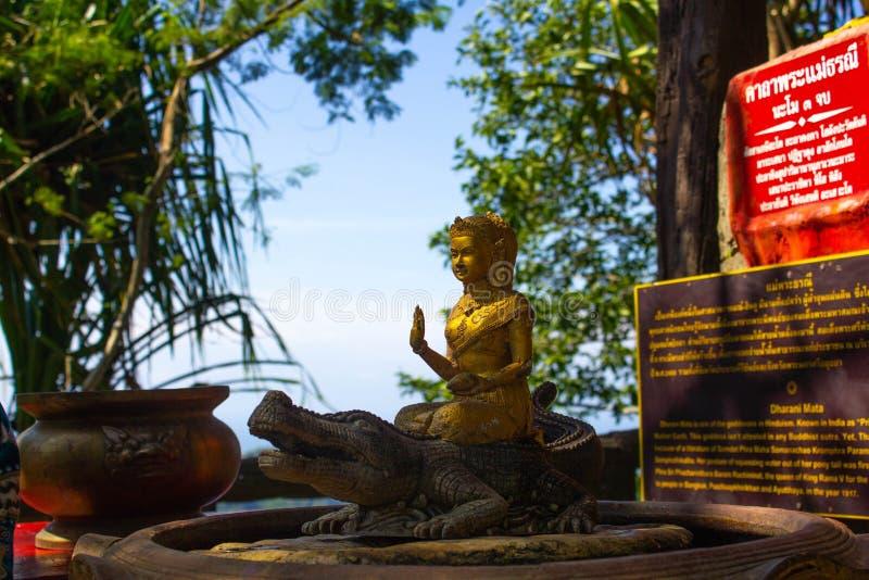 Una piccola statua dorata di Buddha con un primo piano dei tropici Statuetta nel tempio di Buddha in Tailandia immagine stock