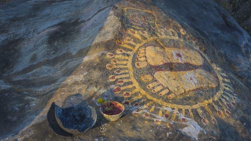 Una piedra con la imagen de las huellas de un gurú encima de la mañana imágenes de archivo libres de regalías