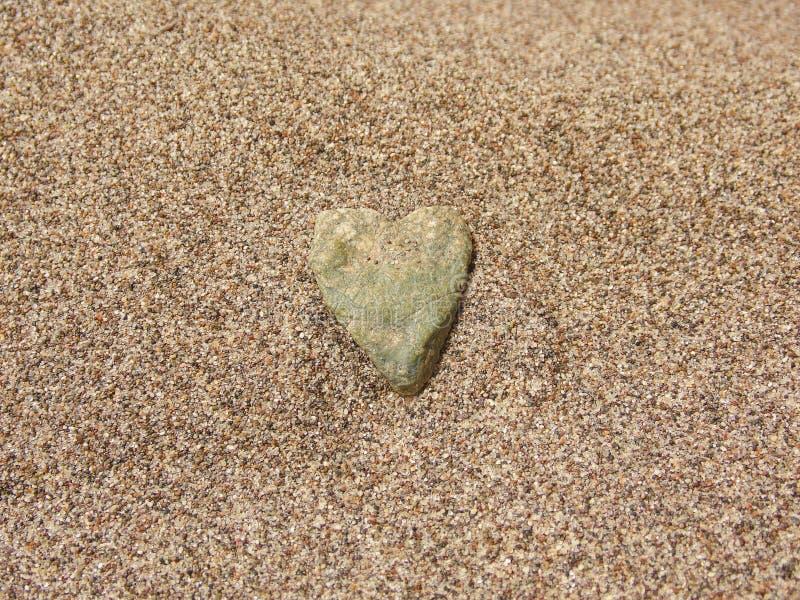 Una piedra en forma de corazón en la arena fotografía de archivo