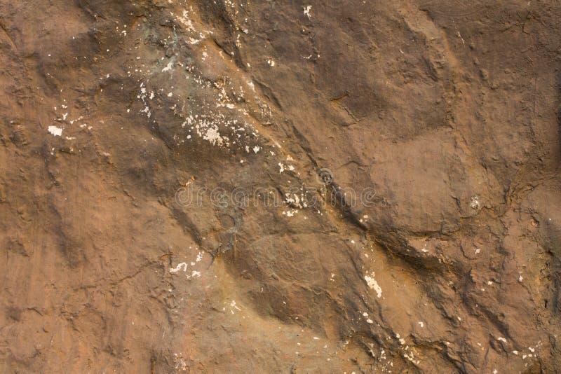 Una piedra marrón gris con alivio profundo, sombras y puntos blancos textura superficial natural foto de archivo libre de regalías