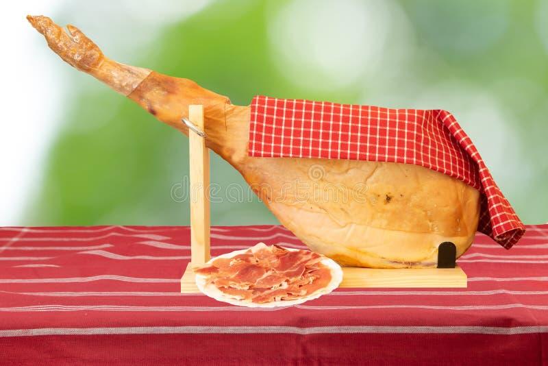 Una pierna delantera de un jamón español de Serrano en el mantel rayado rojo a imágenes de archivo libres de regalías