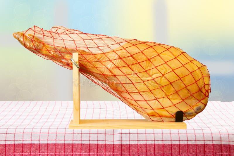 Una pierna delantera de un jamón español de Serrano en el mantel rayado rojo a fotos de archivo libres de regalías