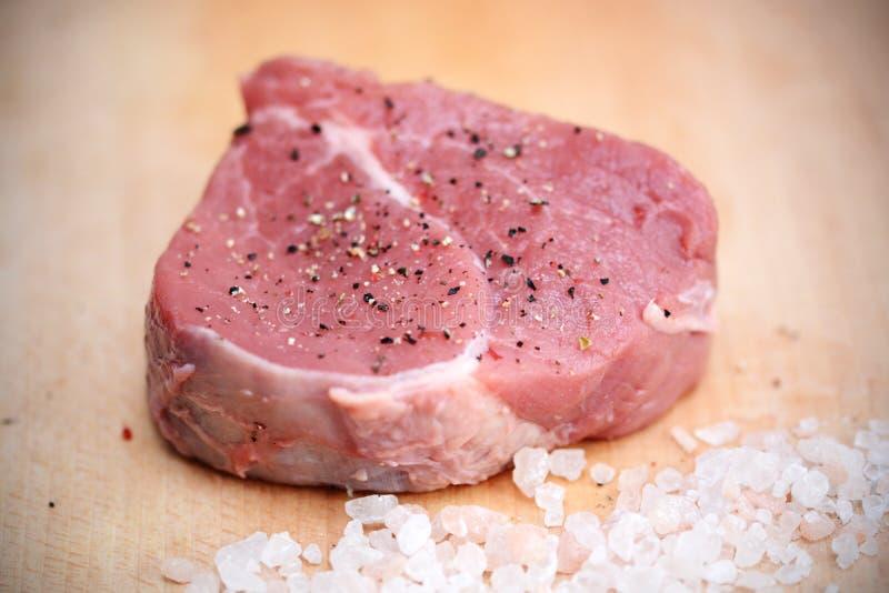 Una pieza de la carne cruda de la carne de vaca en tabla de cortar de madera con pimienta y sal Himalayan rosada foto de archivo