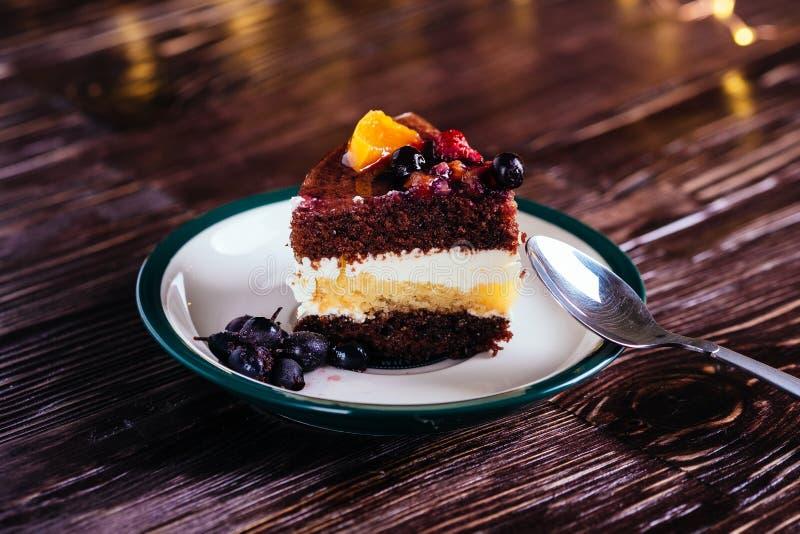 Una pieza de la torta con el postre dulce de las frutas poner crema del chocolate con la cuchara en fondo de madera con las luces fotografía de archivo