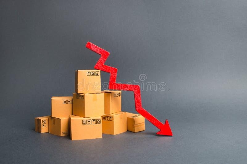 Una pila de cajas de cartón y de una flecha roja abajo La disminución en la producción de mercancías y de productos, el descenso  fotos de archivo libres de regalías