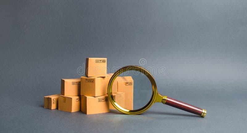 Una pila de cajas y de una lupa Búsqueda del concepto para los bienes y servicios Seguimiento de paquetes Control de calidad serv foto de archivo libre de regalías