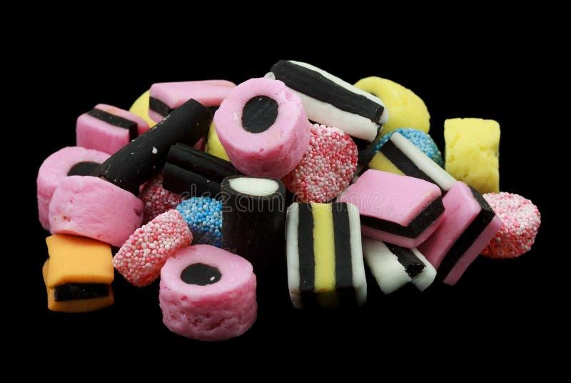 Una pila de caramelo de allsorts del regaliz aislado en fondo negro foto de archivo
