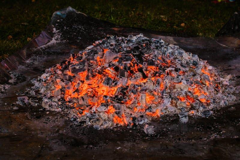 Una pila de carbones que brillan intensamente en la noche fotografía de archivo libre de regalías