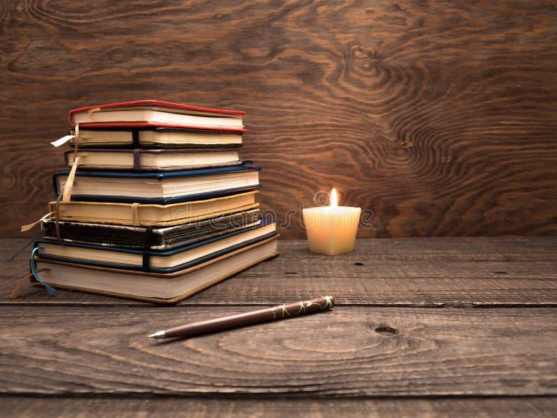 Una pila de cuadernos, de una pluma y de una vela en una tabla de madera foto de archivo libre de regalías