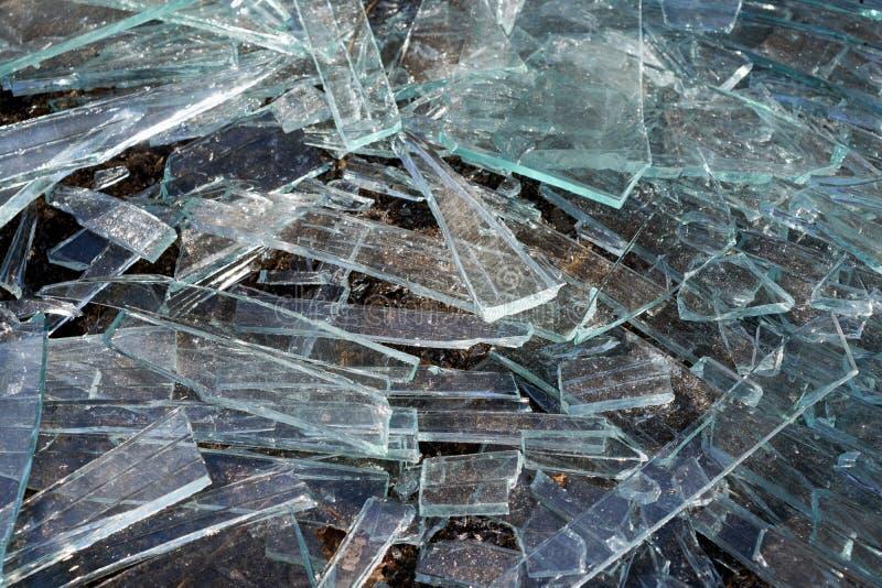 Una pila de diversos pedazos agudos de vidrio quebrado que mienten en la tierra fotografía de archivo libre de regalías