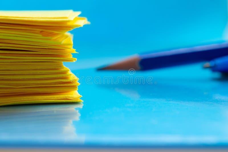 Una pila de documento amarillo y de un lápiz sobre un primer azul de la tabla fotografía de archivo