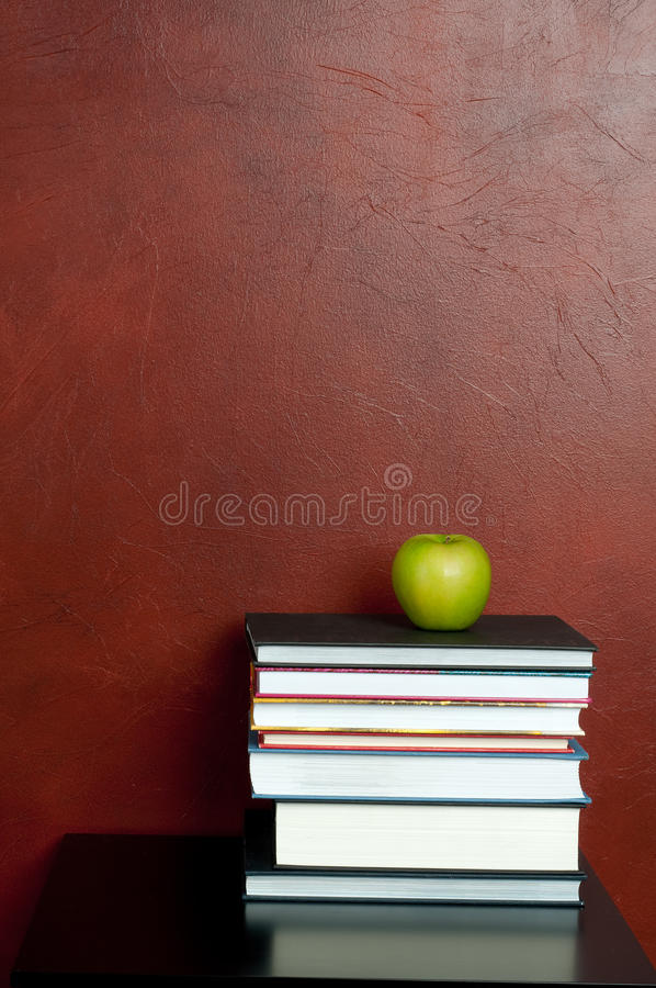 Una pila de libros con una manzana verde fotografía de archivo