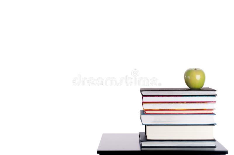 Una pila de libros con una manzana verde en blanco fotografía de archivo libre de regalías