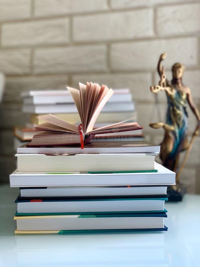 Una pila de libros en la tabla, un libro abierto, libros para un abogado, Themis La diosa de la justicia imagen de archivo libre de regalías