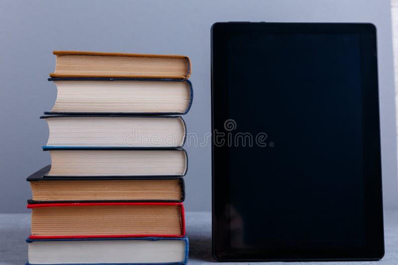 Una pila de libros y de una tableta en un fondo gris El concepto de educación foreground fotografía de archivo libre de regalías