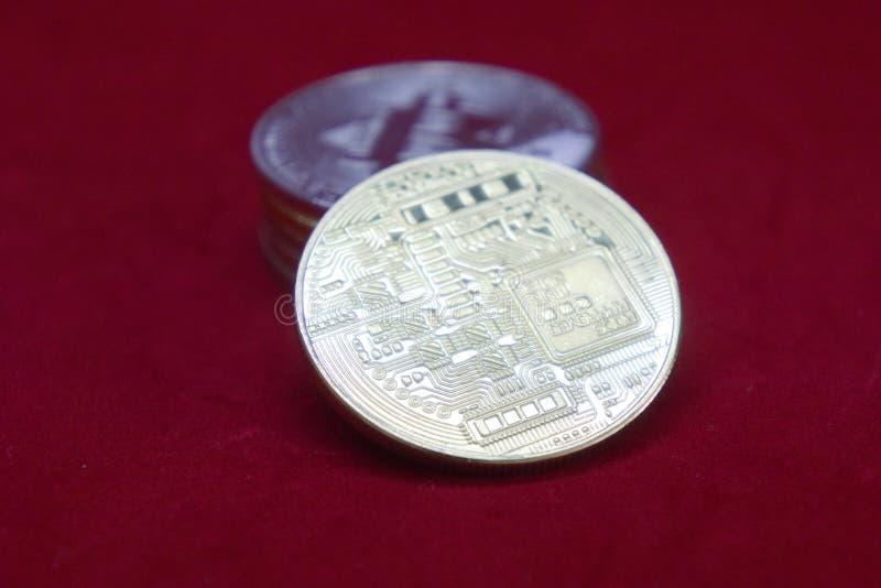 Una pila de oro y de monedas de plata del cryptocurrency con el bitcoin en el frente en un fondo rojo del terciopelo imágenes de archivo libres de regalías