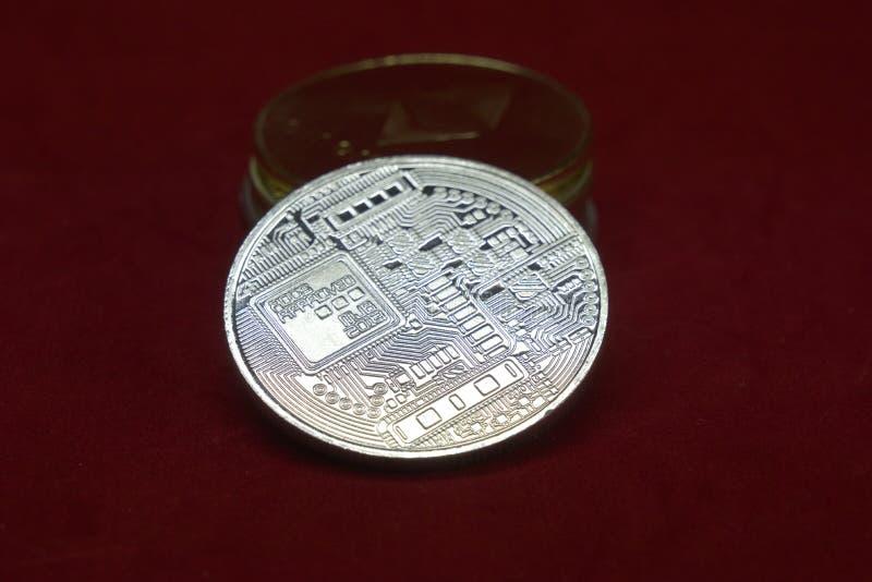 Una pila de oro y de monedas de plata del cryptocurrency con el bitcoin en el frente en un fondo rojo del terciopelo foto de archivo libre de regalías