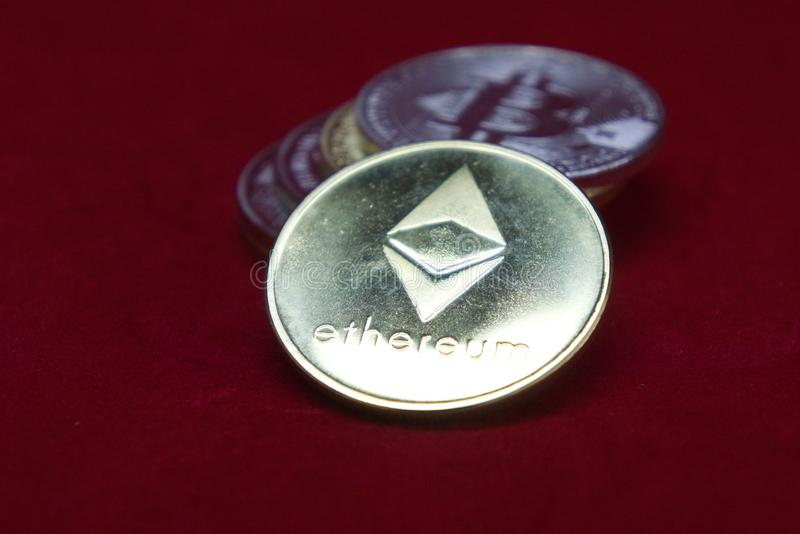 Una pila de oro y de monedas de plata del cryptocurrency con ethereum en el frente en un fondo rojo del terciopelo foto de archivo libre de regalías