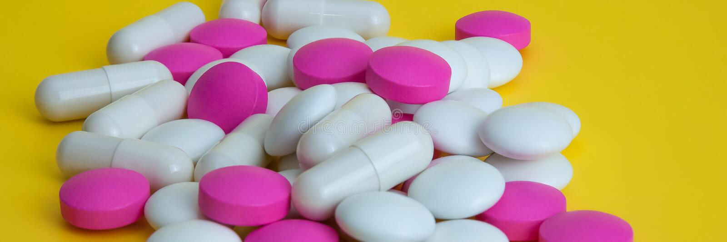 Una pila de píldoras de diversos colores en un fondo amarillo foto de archivo